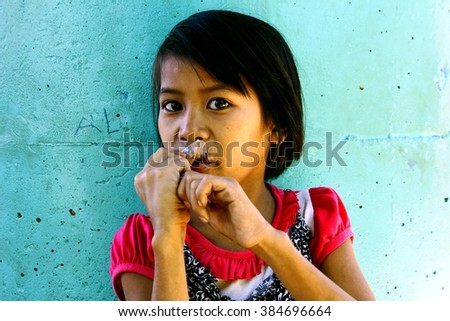 MARIKINA CITY, PHILIPPINES - FEBRUARY 12, 2016: A young girl eats frozen fruit juice from a plastic to refresh her during a hot day. - stock photo