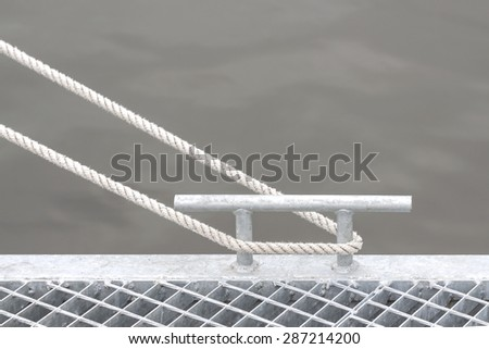 Marina bollard with rope, marine background with space for text. - stock photo