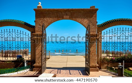 Marina d'Or beach in the Oropesa del Mar resort town. Picturesque view of a beach and Mediterranean Sea, view through the arched gates. Vacation concept. Spain