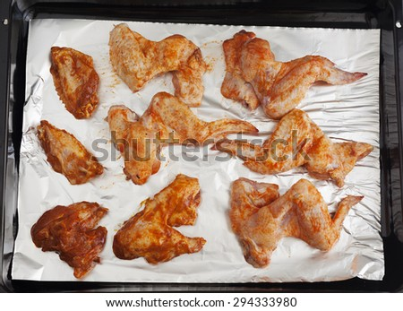 Marinaded hot and spicy raw chicken wings on the oven tray with foil. - stock photo