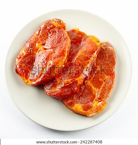 Marinated and seasoned pork neck slices on a plate - stock photo