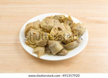 Marinated artichoke hearts on a  white plate atop a wood table.