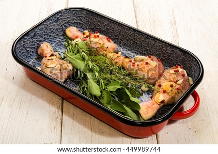 marinated chicken drumstick with red pepper, fresh garden herbs, garlic and himalaya salt in a roasting tin  - stock photo