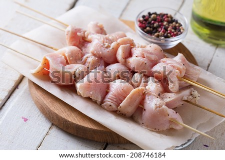 Marinated chicken meat on skewers ready to cook. Selective focus. Rustic style.  - stock photo