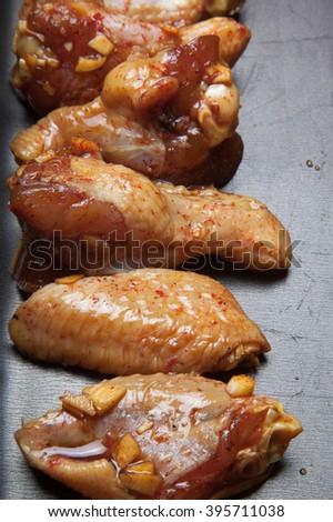 Marinated chicken wings on a black pan. Selective focus. - stock photo