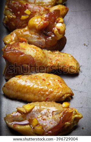 Marinated chicken wings on a black pan. Selective focus. Toned. - stock photo