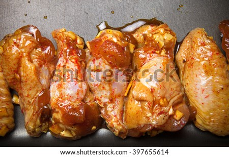 Marinated chicken wings on a black pan. Toned. - stock photo