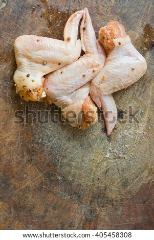 marinated Chicken wings with pepper on chopping block background - stock photo