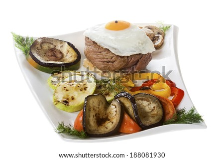 Marinated fillet steak with egg and grilled vegetables on the plate. - stock photo