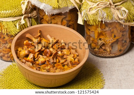 Marinated golden chanterelles in jars and in a bowl - stock photo