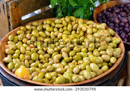 Marinated green and black french olives in big pot at the rural market. Provence, France