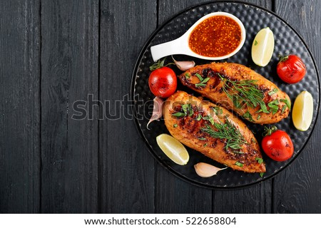 Marinated grilled  chicken breasts cooked and served with fresh herbs and lime juice on a wooden board.