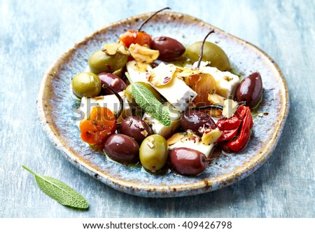 Marinated habanero peppers, olives and feta cheese on a ceramic plate (mediterranean-style antipasto)  - stock photo