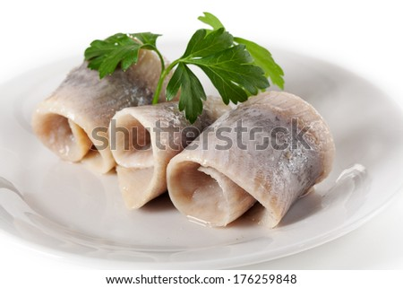 Marinated herrings served with persil on a plate - stock photo