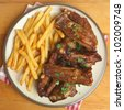 Marinated pork ribs and fries - stock photo