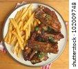 Marinated pork ribs and fries - stock photo