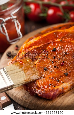 Marinated pork steak on cutting board and ingredients  for cooking