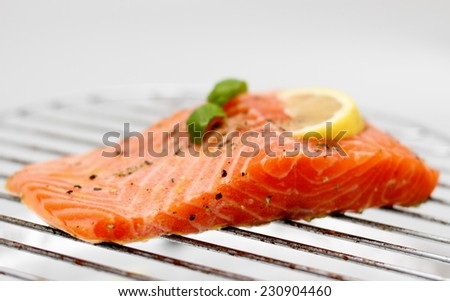 Marinated salmon fillet with lemon on grill, soft focus, horizontal - stock photo