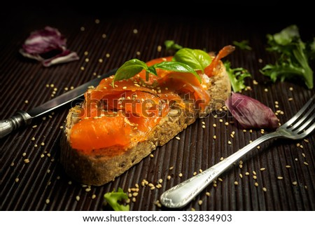 Marinated salmon with basil and sesame seeds on slice of bread