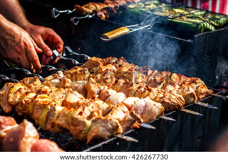 Marinated shashlik preparing on a barbecue grill over charcoal. Shashlik or Shish kebab popular in Eastern Europe. Shashlyk (skewered meat) was originally made of lamb. Roast Beef Kebabs On BBQ Grill. - stock photo