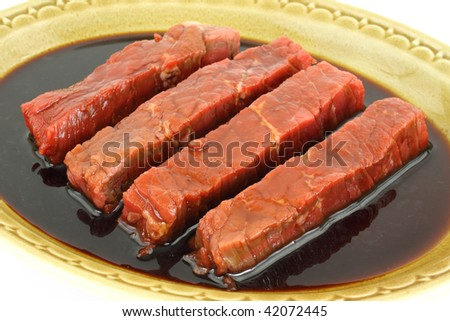 Marinated steak strips in old dish - stock photo