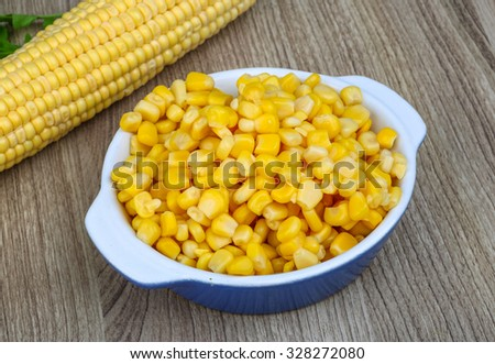 Marinated sweet yellow corn in the bowl on wood background