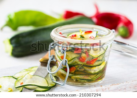 Marinated zucchini salad canned in glass jar - stock photo