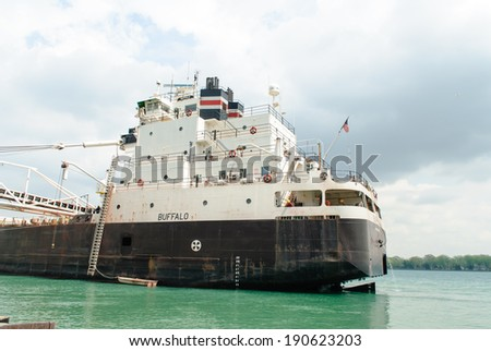 MARINE CITY, MI - USA - MAY 13, 2014: The BUFFALO of the American Steamship Company, on May 13, 2014 unloads limestone product at a stone yard in Marine City, MI. The BUFFALO sails the Great Lakes.