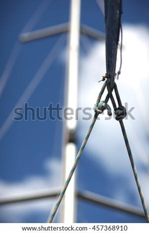 Marine cordage on background of mast and blue sky - stock photo