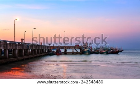 Marine dock and fishing ships at sunset, Thailand - stock photo
