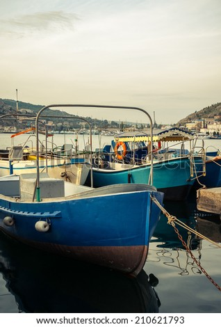 Marine landscape with a boats in harbor. Old boats on pier - fisherman's transport. Bow of the fishing boat with reflection on sea surface. Blue motorboats are moored in harbor.