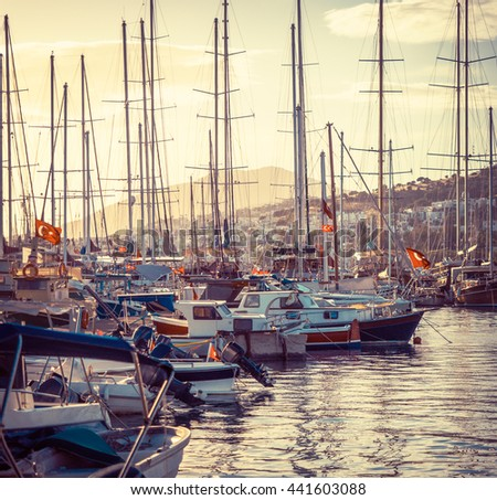 Marine landscape with modern yachts in a Bodrum harbor. Beautiful sailboats in lagoon at sunset. Marina with yacht-club for luxury leisure on riviera of Aegean. Travel and sea vacation in Turkey. - stock photo