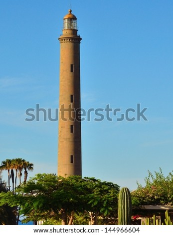 Marine landscape with the emblematic Maspalomas lighthouse on a splendid blue sky and between varied vegetation, Gran canaria, Canary islands, Spain