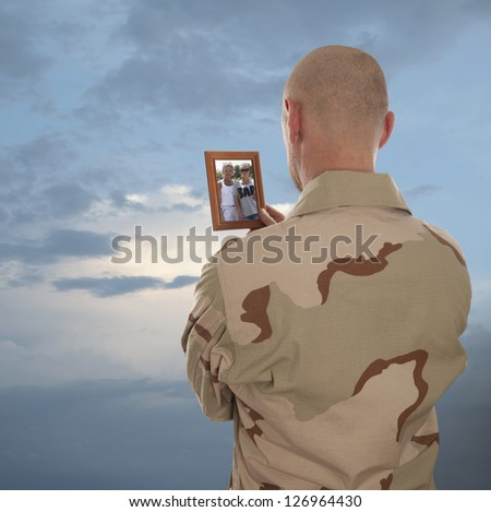 Marine looks at the picture of the family - stock photo