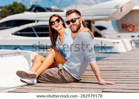Marine lovers. Cheerful young couple smiling and looking at camera while sitting on wooden pier  - stock photo