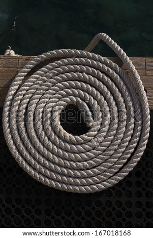 Marine mooring rope coiled on a dive centre jetty, Bonaire, Netherlands Antilles - stock photo