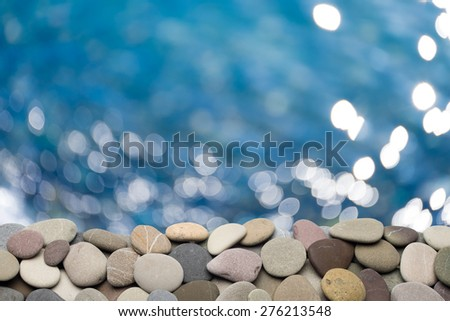Marine pebbles on out-of-focus sea background. - stock photo