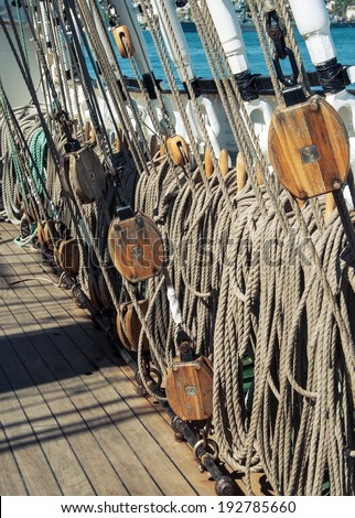 Marine ropes and tackles on the tall ship from sea journey. Rigging details on mast of the old sailboat. Old wooden block with rope on the sail. Marine pulley closeup on the old vessel. - stock photo