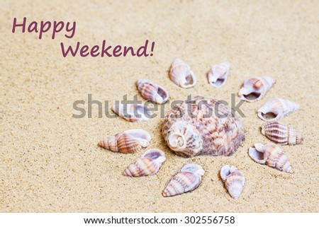 "Marine shells  on the  sand, sea mood wallpaper; Vacations , holidays, traveling background, ""Happy weekend!"" inscription - stock photo"