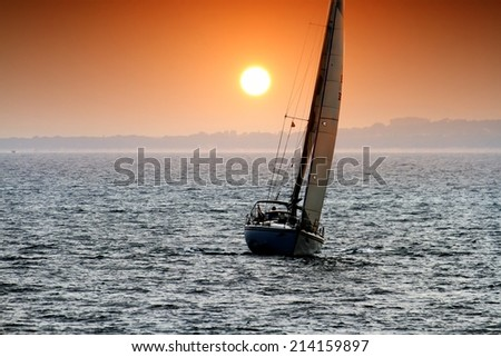 Marine sunset scene with a sloop