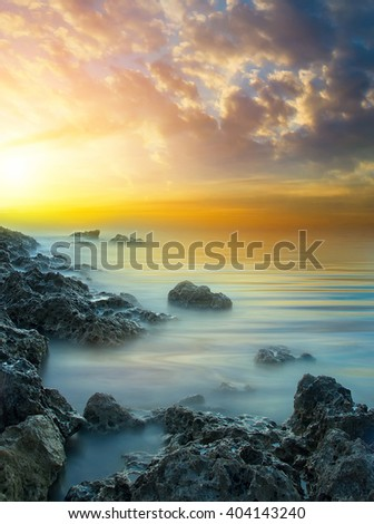 Marine sunset with a glow of the sun, with stones and a calm sea water. Natural landscape