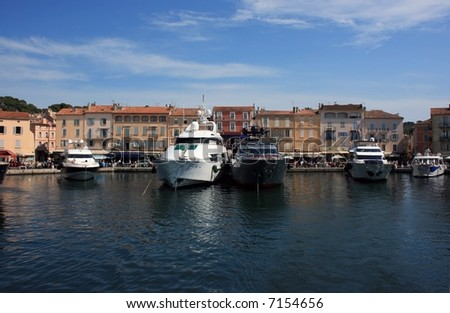 Marine view of Saint Tropez quay with luxury yachts and colorful houses