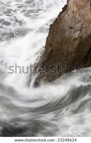 Marine wave moved by effect of the long exposure breaking against a rock and creating a whirlpool together with it - stock photo