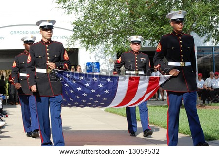 Marines carrying flag at Memorial Day ceremony - stock photo