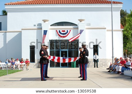 Marines getting ready to fold and present American flag at Memorial Day ceremony - stock photo