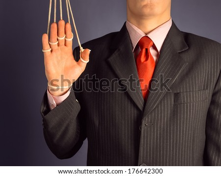 Marionette businessman makes a welcome gesture, hand on the ropes - stock photo