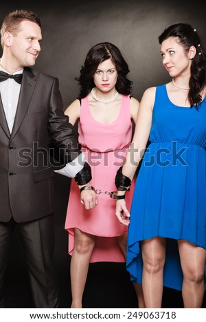 Marital infidelity concept. Love triangle two women one man passion of love hate. Mistress betrayal within the family. Black background. - stock photo