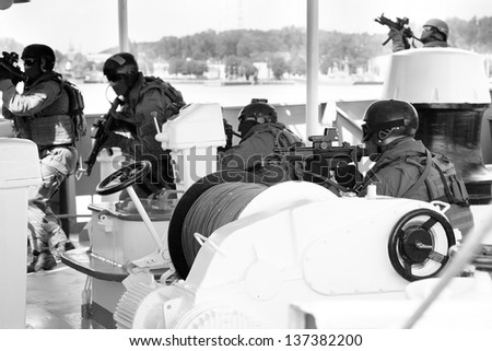 Maritime commando � soldier. The Marine special forces to enter the ship to its search and hostage rescue � exercises. In the action. Black and white photo with film grain. - stock photo