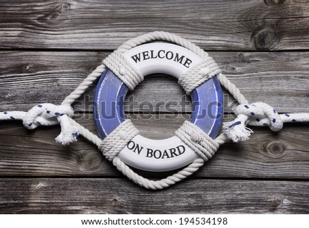 Maritime decoration - life belt on wooden background - concept for sailing, cruising or teamwork.  - stock photo