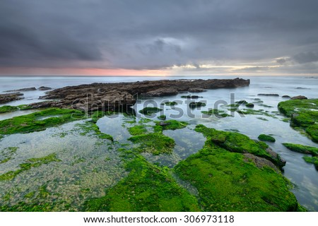 Maritime landscape at sunset. Rocky beach on the west coast of Portugal, in the atlantic ocean. Holiday destination and a tourist attraction. Horizontal photograph taken with long exposure effect.